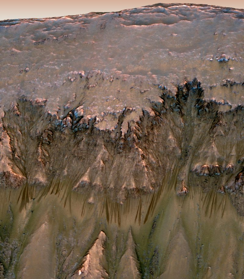 Long, thin dark streaks below triangular features on crater wall.