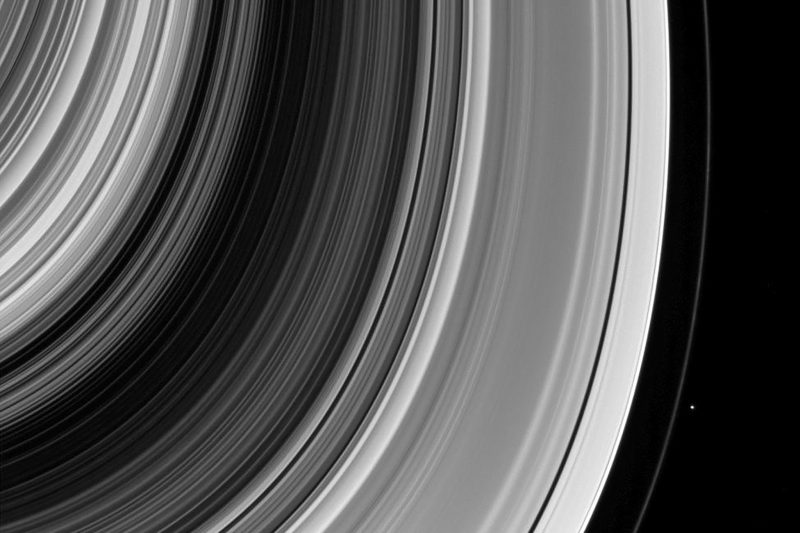 Very many rings of Saturn with a tiny dot outside the outermost visible one.