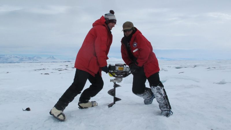 Two heavily-clothed scientists straining to twist a large auger into the ice.