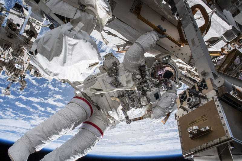Space-suited astronaut a foreground, ISS machinery, upside-down Earth in background.