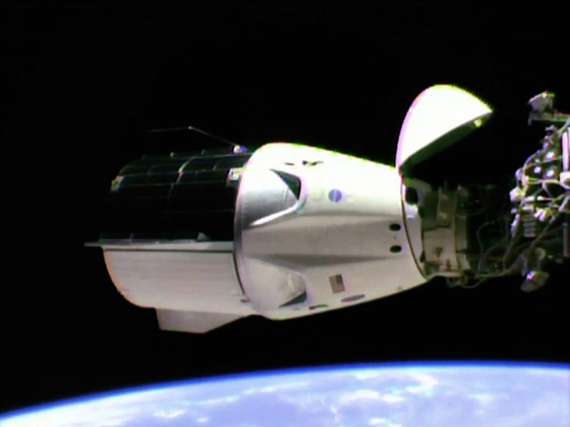White, cylindrical spacecraft attached to ISS machinery on right side.
