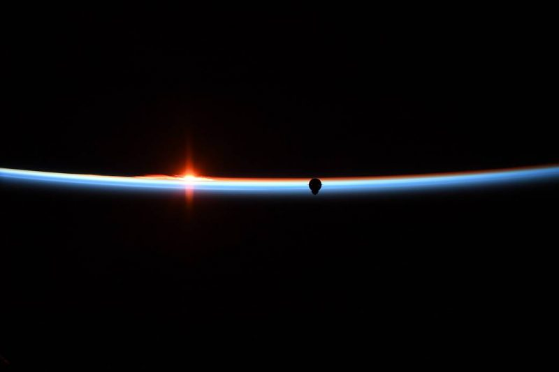 Narrow curve of crescent Earth horizon with dark spot against it on right.