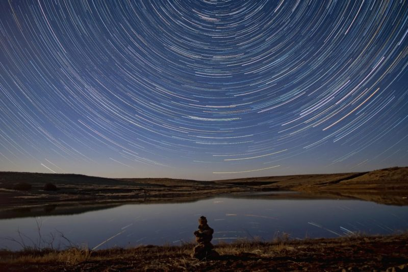Timelapse of stars wheeling around the North Star, with a mountain-rimmed, above-ground reservoir in the foreground.
