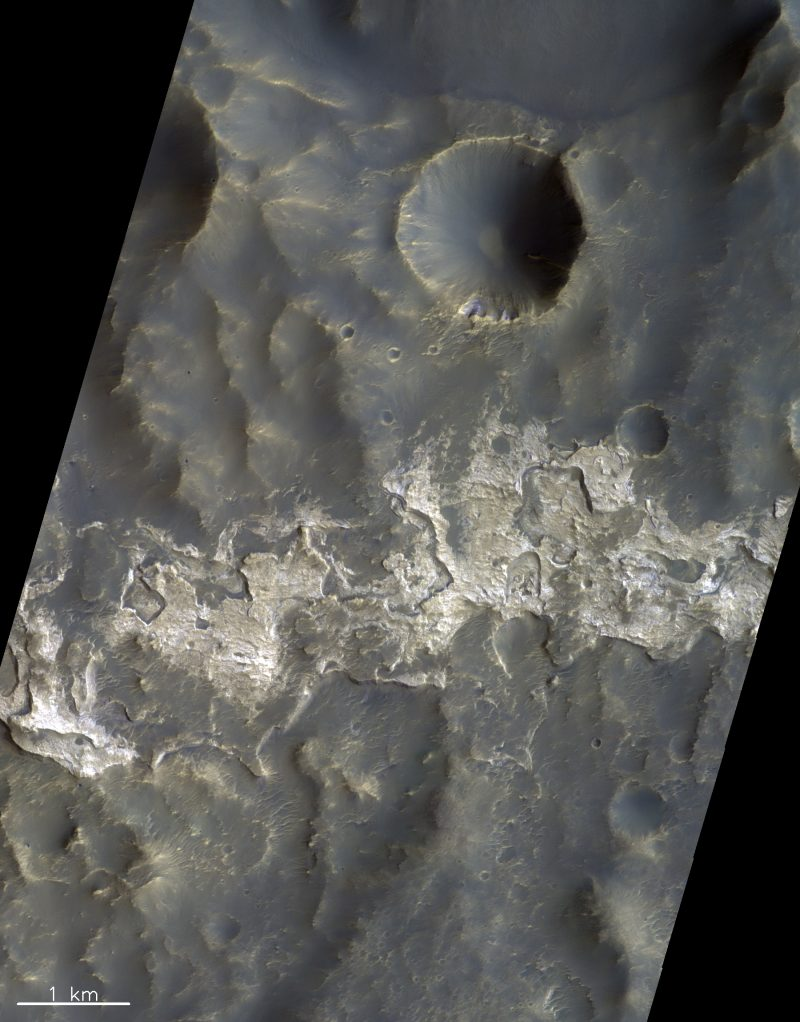 Bright irregular wide streak against dark gray surface with craters.