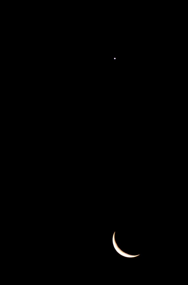 Bright Venus and thin crescent moon, on black background.