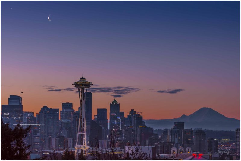 Cityscape - Seattle - large tower and conical mountain in background with Venus and moon above.