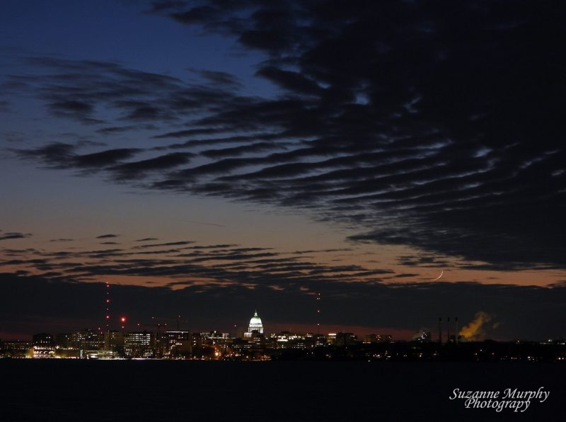 Very thin crescent moon over cityscape with illuminated capitol building.
