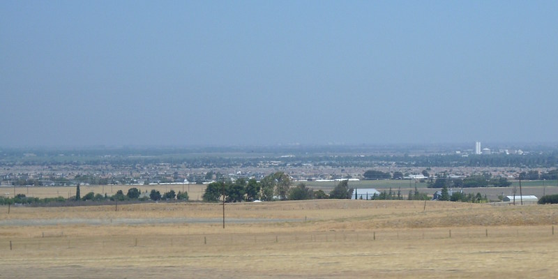 Flat land, brownish up close, line of trees and structures in distance.