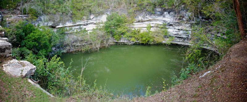 Round cliff-sided pool with green water on Earth.