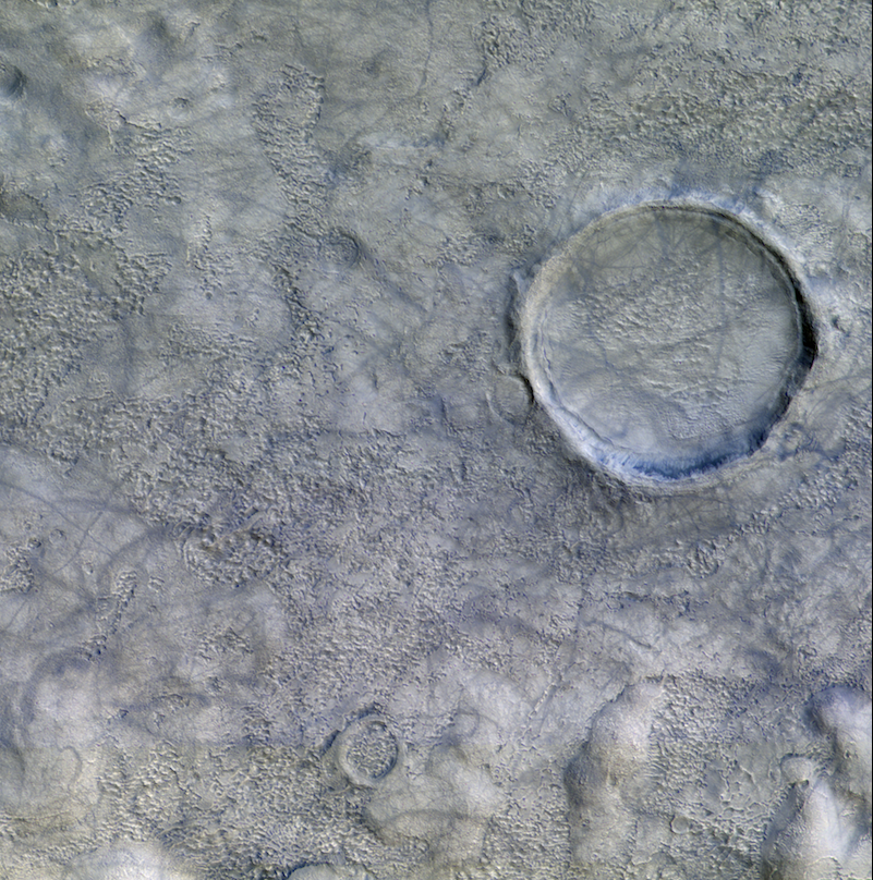 Large crater on gray stippled surface criss-crossed with many bluish lines.