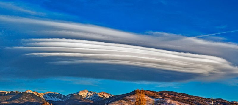Wide multiple-layer lenticular cloud over mountains.