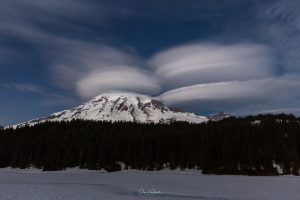 Several lenticular clouds above and beside snow-capped peak.