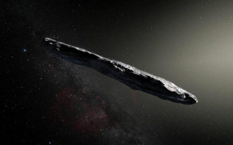 Long, thin, irregular surface space rock illuminated on one side.