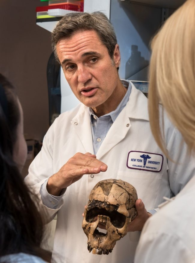 Rodrigo Lacruz in lab coat holding a human skull, talking to a person just out of view.