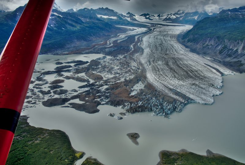 Front edge of glacier seen far below red strut of plane.
