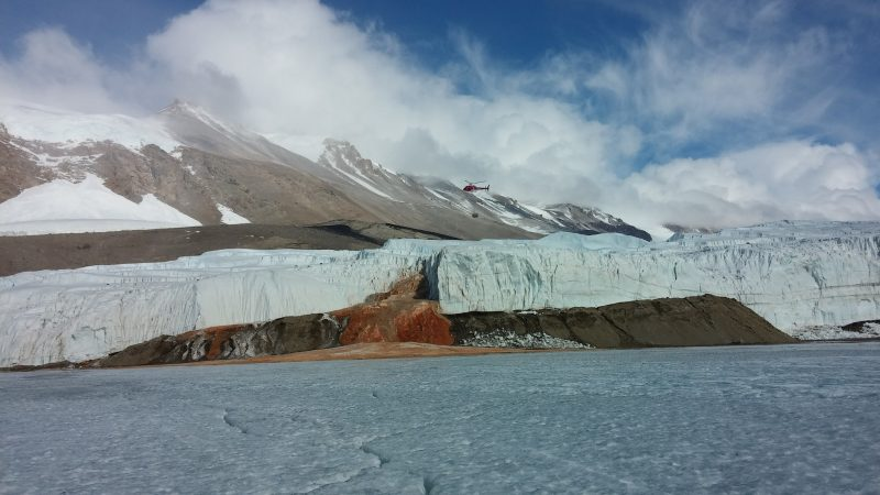 Ice field in foreground, glacier edge in background, reddish waterfall.