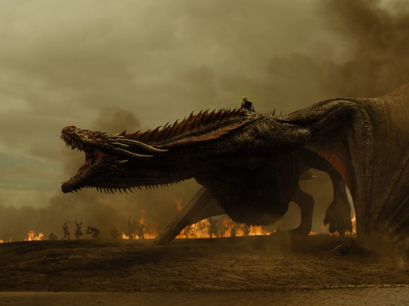 Front end of large bellowing dragon with warriors and fires in distance.