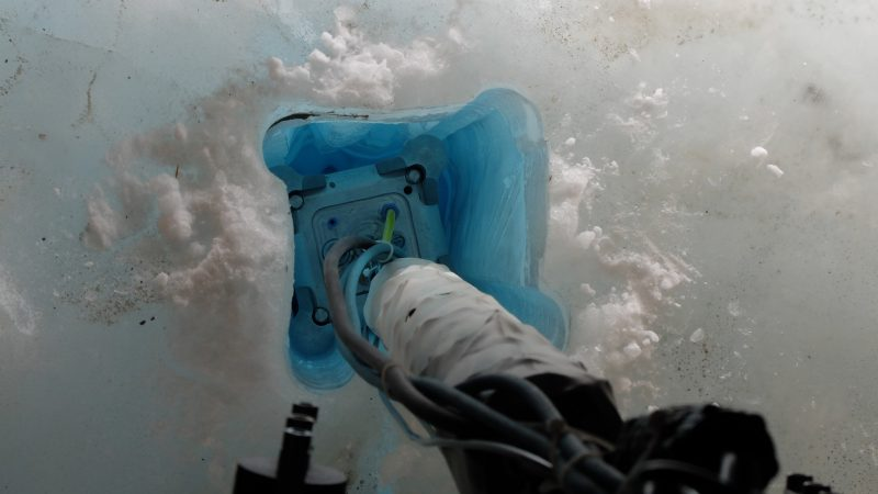 Machine arm pressing square end into square hole in blue ice.