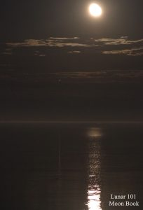 A waning gibbous moon and bright Jupiter shining over a lake, with long reflections of each cast on the water.