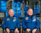 Identical twin male astronauts sitting next to each other.