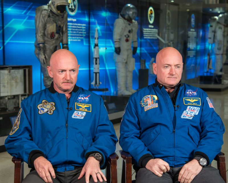 Bald middle-aged identical twin male astronauts sitting next to each other.