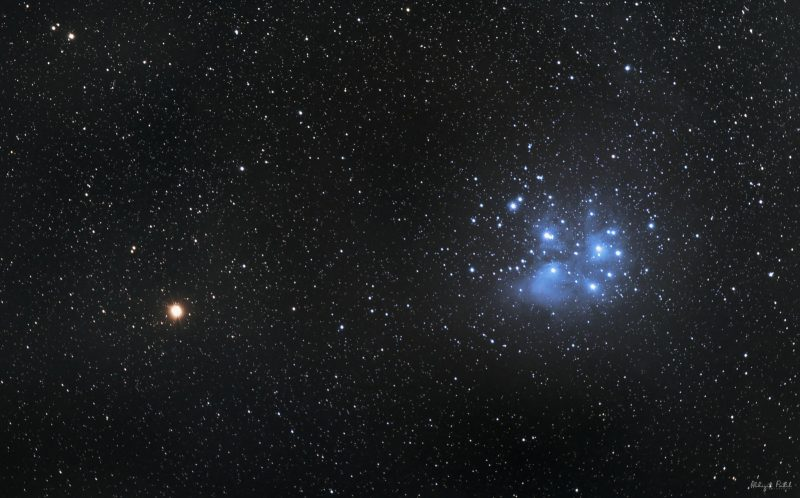 A red starlike point, Mars, next to a bluish dipper-shaped star cluster, the Pleiades.