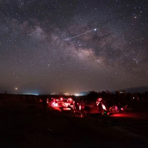 """A """"star party,"""" at night, with red flashlights illuminating a group scattered around telescopes, with a bright streak passing overhead."""