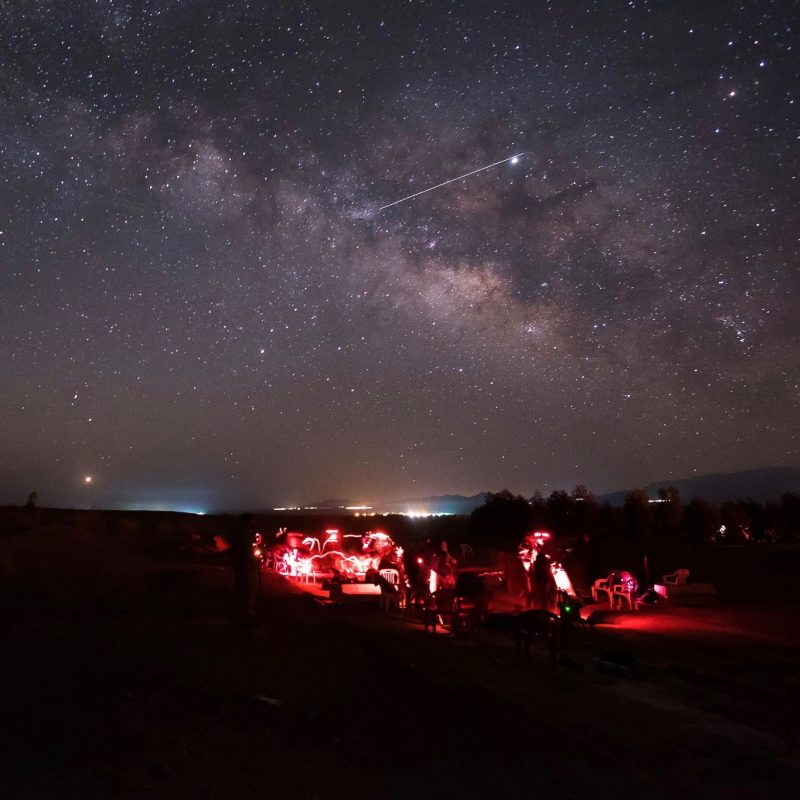 At night, people with red flashlights grouped around telescopes, stars above, with bright streak in the sky.