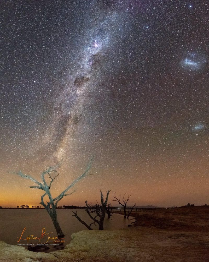 Milky Way and 2 small glowing oblongs, the Magellanic Clouds, over a lake and some bare trees.