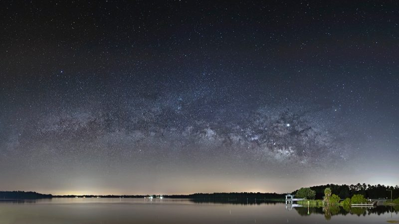 Horizontal bright cloudy looking Milky Way with bright dot over a lake.