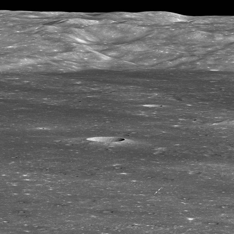 Moon landscape with mountains on horizon and craters closer to observer.