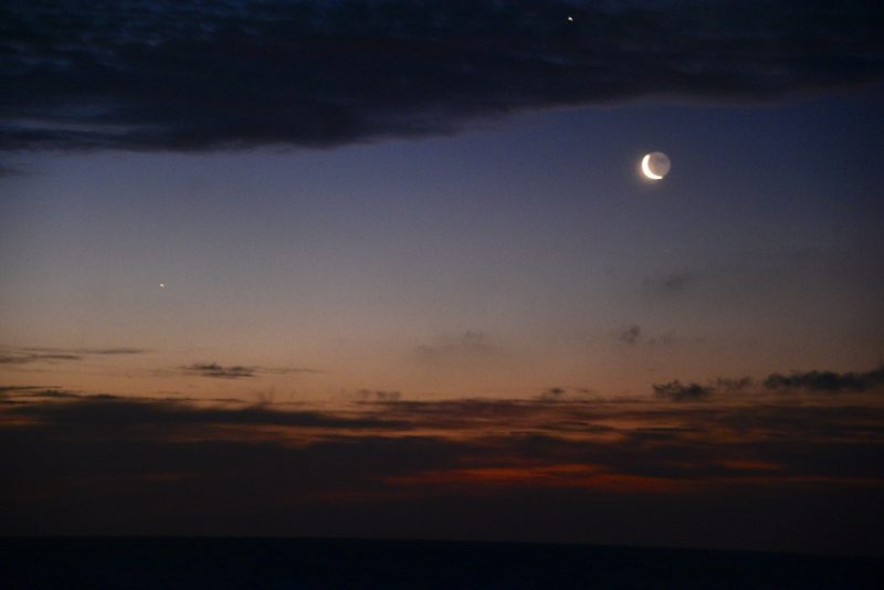 Venus high up, moon, Mercury among torn clouds above sea.