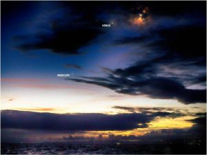 Party cloudy dawn above the ocean, with the moon and 2 planets.
