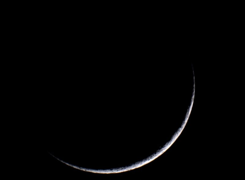 Close-up of a thin waxing crescent moon.