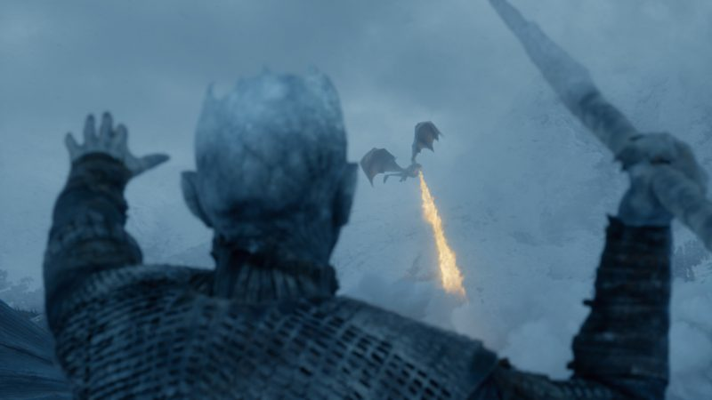 Back of spear-holding Night King with winged dragon breathing fire in distance.
