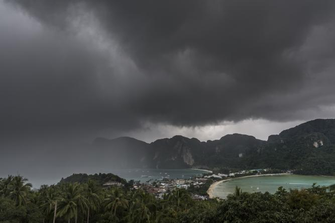 Heavy, dark thunderclouds over mountainous island with crescent beach visible.