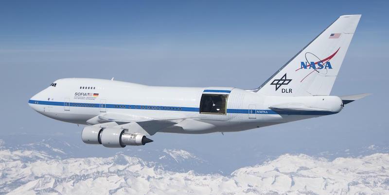 Large white jet airplane in flight with black rectangular opening, NASA logo on tail.