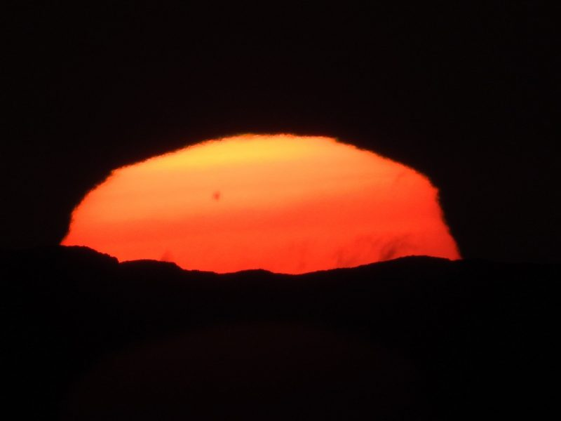 Flattened setting sun, with large sunspot visible.