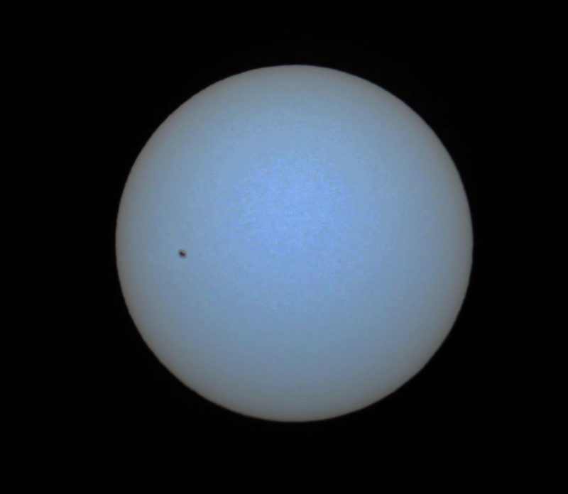 Full disk of pale blue sun through blue filter, with sunspot.