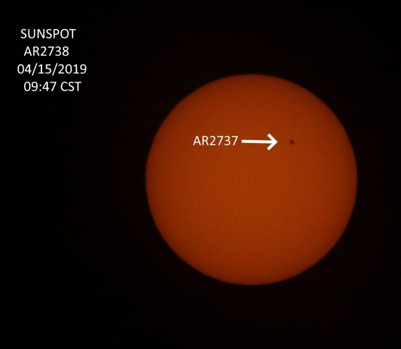 Sun with small sunspot labeled with arrow pointing at it.
