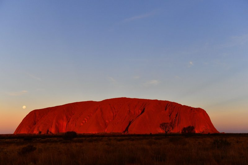 Huge mesa-like dark orange rock formation glowing in sunset with tiny white full moon beside it.