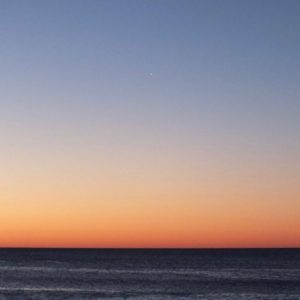 A sea horizon in bright twilight, with Venus barely visible.