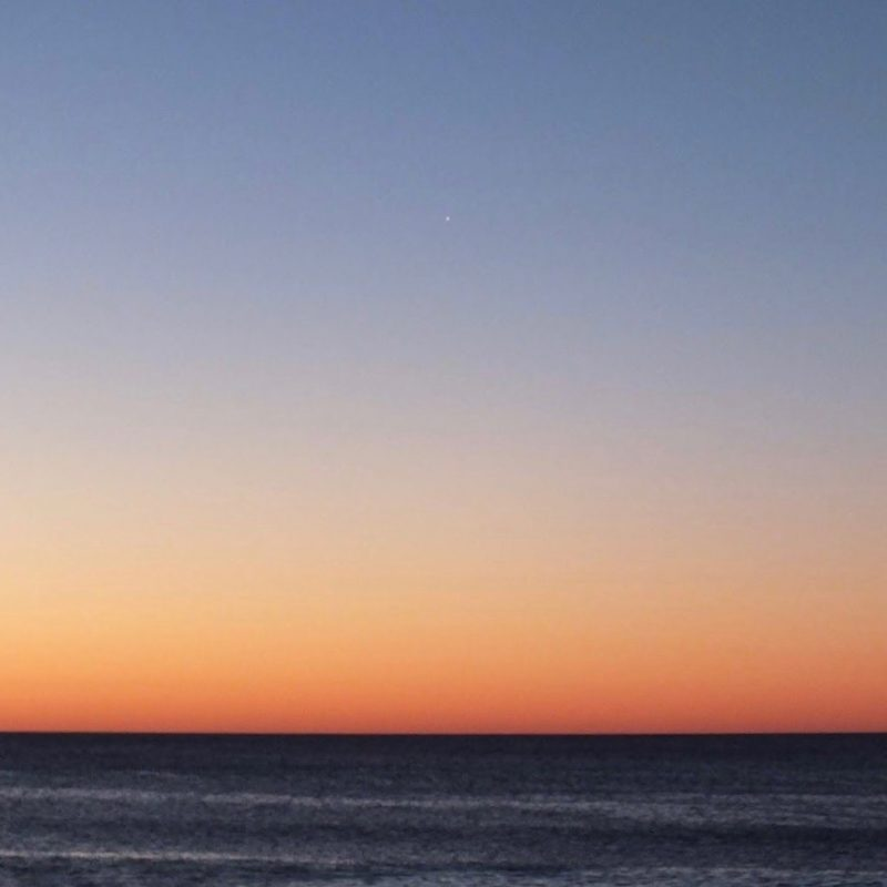 A sea horizon in bright cloudless twilight, with Venus barely visible.