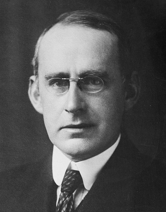 Black and white photo of a man with glasses.