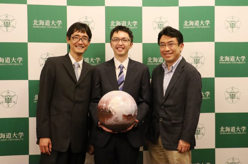Three Japanese scientists in suits, one holding a basketball-sized model of Pluto.