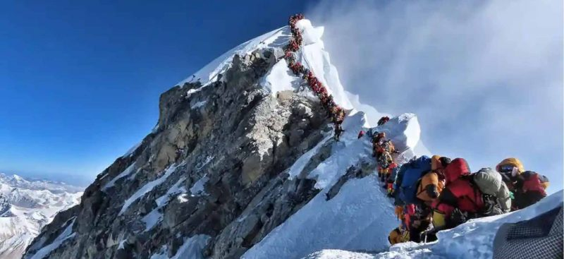 A craggy, snowy peak in the background, and a long single-file line of hikers ascending to the peak.