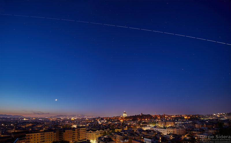 A bright streak above the Rome city lights in deep blue twilit sky.