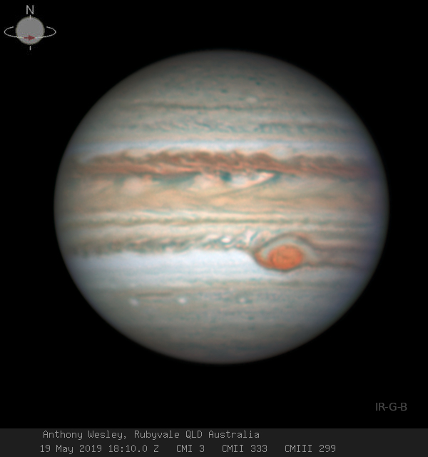 Immense globe of Jupiter with horizontal bands and large orange oval in lower right.