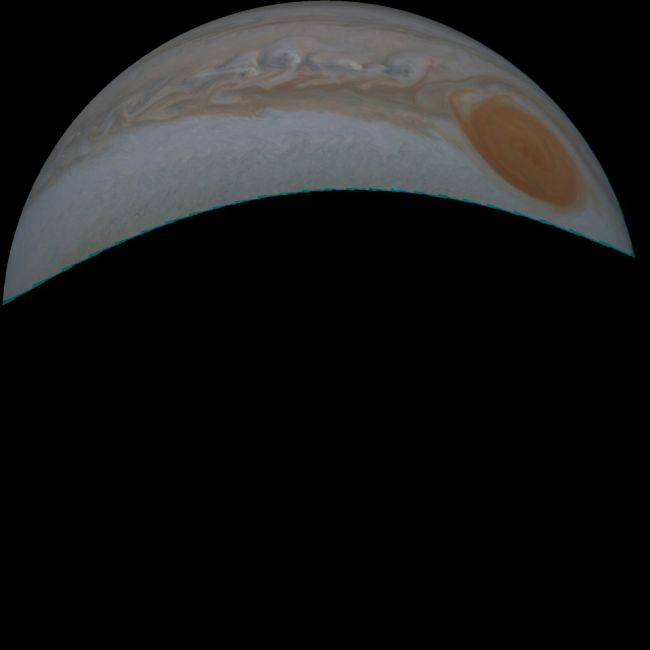 Crescent of Jupiter and very large, orange oval in one end of crescent.