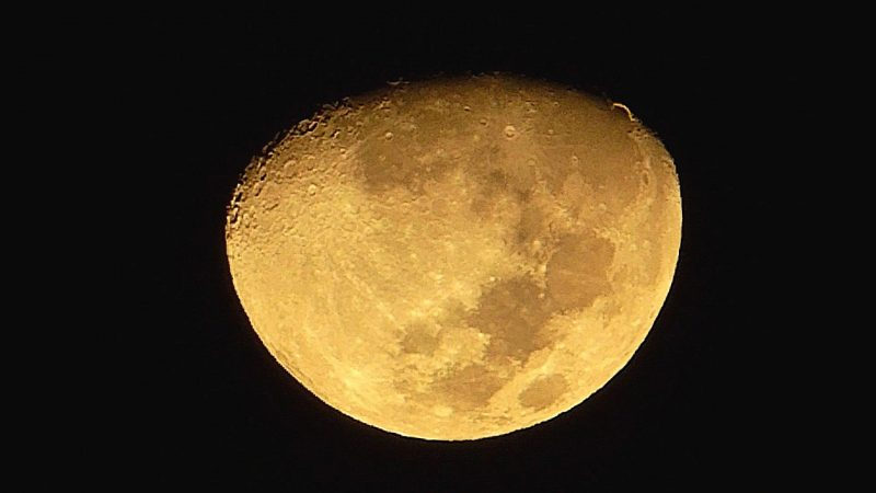Golden-colored waxing gibbous moon, with a short thin line arc out from the edge at upper left.